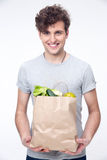 Happy man holding a bag full of groceries. Over gray background Stock Photo