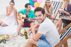 Happy man holding beer and smiling while sitting with his friends Royalty Free Stock Image