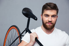 Happy man holding bicycle on the shouder. Portrait of a happy man holding bicycle on the shouder over gray background Royalty Free Stock Photo