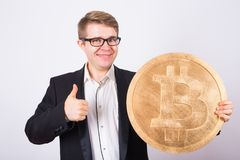Happy man holding big bitcoin and showing thumbs up stock images