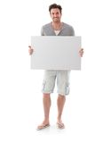 Happy man holding blank sheet smiling. Happy young man holding a blank sheet in hand, smiling Stock Image