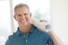 Happy Man Holding Blueprint In New House. Portrait of happy mature man holding blueprint in new house Stock Images