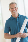 Happy Man Holding Blueprint In New House. Portrait of happy mature man holding blueprint while standing in new house Royalty Free Stock Image