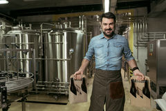 Happy man holding bottles of alcohol in brewery Stock Photos