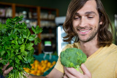 Happy man holding broccoli and bunch of herbs and in organic section Royalty Free Stock Image