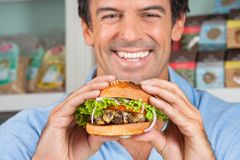 Happy Man Holding Bugger In Grocery Store Royalty Free Stock Photography
