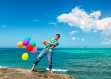 Happy man holding bunch of colorful air balloons at the beach Stock Image