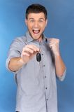 Happy man holding car keys on blue background. Royalty Free Stock Image