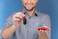 Happy man holding car keys on blue background. Stock Image
