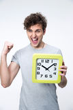 Happy man holding clock with arms raised Stock Photography