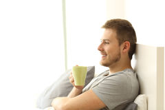 Happy man holding coffee cup on the bed. Side view of a happy man holding coffee cup having breakfast and thinking on the bed of an apartment Stock Photos