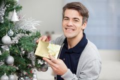 Happy Man Holding Gift By Christmas Tree Royalty Free Stock Photo