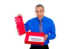 Happy man holding gift with health care reform sign inside Stock Photography