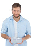 Happy man holding a gift looking at camera Stock Image