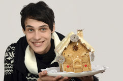 Happy man holding a gingerbread house. Royalty Free Stock Images