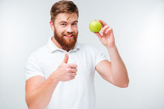 Happy man holding green apple and showing thumbs up gesture Royalty Free Stock Photo