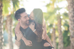 Happy man holding his girlfriend on back in sunlight Royalty Free Stock Image