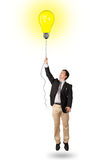 Happy man holding a light bulb balloon Stock Photos