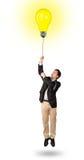 Happy man holding a light bulb balloon Stock Photos