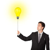 Happy man holding a light bulb balloon Royalty Free Stock Photos