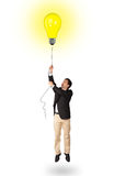 Happy man holding a light bulb balloon Stock Image