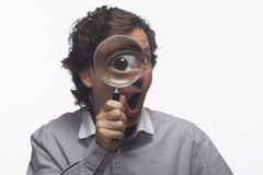 Happy man holding magnifying glass up to his eye,horizontal Stock Photo