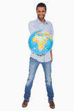Happy man holding out a globe Stock Image
