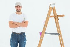 Happy man holding paint roller while standing by ladder Royalty Free Stock Photos