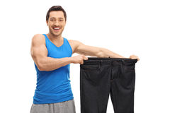 Happy man holding a pair of oversized pants. Isolated on white background stock photography