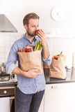 Happy man holding paper grocery shopping bag in the kitchen Stock Photo