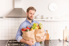 Happy man holding paper grocery shopping bag in the kitchen Royalty Free Stock Photos