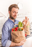 Happy man holding paper grocery shopping bag in the kitchen Stock Photos