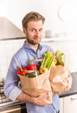 Happy man holding paper grocery shopping bag in the kitchen Royalty Free Stock Image
