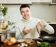 Happy  man holding raw steak of fish Stock Image