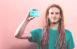 Happy man holding a retro cassette tape royalty free stock images