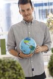 Happy man holding small globe Royalty Free Stock Images