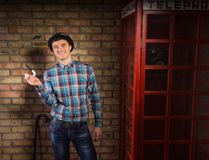 Happy Man Holding Smoking Pipe Near Phone Booth Royalty Free Stock Image