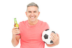 Happy man holding a soccer ball and a beer Royalty Free Stock Photography