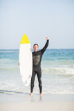 Happy man holding a surfboard on the beach. With his hand raised Royalty Free Stock Photos