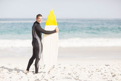 Happy man holding a surfboard on the beach. At sunny day Royalty Free Stock Image