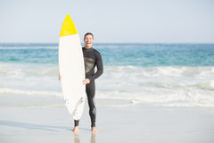 Happy man holding a surfboard on the beach Royalty Free Stock Images