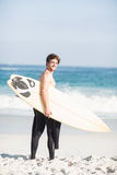 Happy man holding a surfboard on the beach. At sunny day Stock Photography