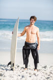 Happy man holding a surfboard on the beach. On a sunny day Royalty Free Stock Photo