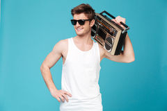 Happy man holding tape recorder. Image of young happy man standing over blue isolated background holding tape recorder. Looking aside Royalty Free Stock Images