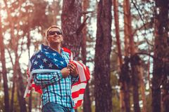 Happy man holding USA flag. Celebrating Independence Day of America. July 4th. Man having fun. Happy man holding USA flag in park at sunset. Celebrating royalty free stock photo