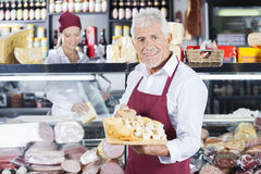 Happy Man Holding Various Cheese On Board In Store. Portrait of happy senior men holding various cheese on cutting board with colleague in background at store Royalty Free Stock Photography