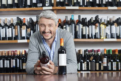 Happy Man Holding Wine Bottle While Leaning On Table. Portrait of happy mature man holding wine bottle while leaning on table in shop Stock Photo