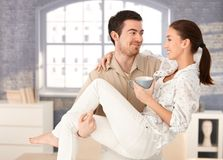 Happy man holding woman in his arms smiling Royalty Free Stock Images