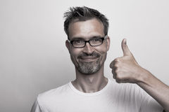 Happy man holds one thumb up. Agreeing man with stubbly beard holds his thumb up Royalty Free Stock Images