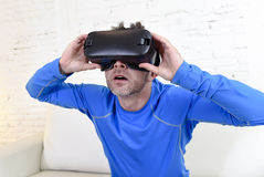 Happy man at home living room sofa couch excited using 3d goggles watching 360 virtual reality Stock Images